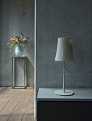 Table lamp on bedside cabinet against exposed concrete wall and vase of exotic flowers on small metal table in background