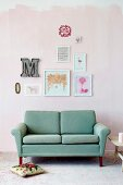 Hand-crafted artworks in various frames and ornamental letters on pink-painted wall above turquoise retro sofa