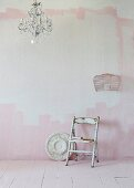Vintage chair against wall carelessly painted pink and white