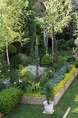 Stone-edged flowerbed and trees in garden