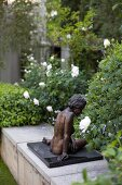 Bronze sculpture on low wall in garden; white roses in background