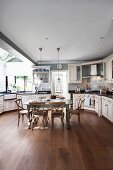 Large kitchen with fitted cupboards and rustic, country-house-style dining set