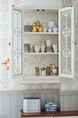 Crockery cabinet with open door built into niche