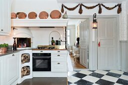 White country-house-style kitchen counter with integrated fireplace and copper pans on sill of mantel hood