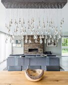 Pendant lamp with suspended glass droplets above dining table in front of grey sofa and fireplace in lounge area