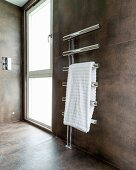 White towel on heated chrome towel rail in modern bathroom with large tiles