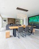 Graue Freischwinger an Holztisch mit Metallgestell, oberhalb Pendelleuchte mit abgehängtem, leuchtendem Glasschmuck in offenem, modernem Wohnraum