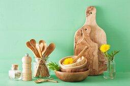 Küchenutensilien aus Holz und Löwenzahnblüten