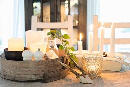 Wintry arrangement of lit candles on table