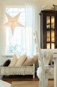 Illuminates paper star in window above cushions in old dolls' bed