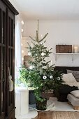 Simply decorated Christmas tree next to cable reel and armchair
