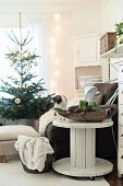 Cable reel used as side table next to armchair and Christmas tree in background