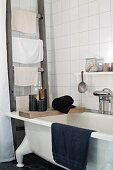 Candles on wooden board on free-standing bathtub next to old ladder used as towel rack