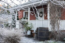 Brick house with veranda in frosty, wintry garden