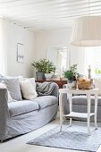 White-painted side table, comfortable couch and pendant lamp with wwhite fabric lampshade in corner of simple living room