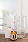 Tealights in holders and glass jar in front of white paper star