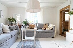Couch and white-painted side table below pendant lamp with white fabric lampshade in rustic living room