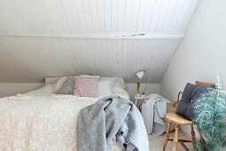Lace bedspread on double bed below sloping ceiling with white wood cladding