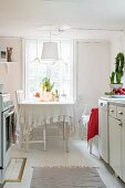 Rustic kitchen with dining set below window and simple pendant lamp with fabric lampshade