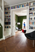 Foot of staircase in library with fitted bookcases, open sliding door and view of man standing between chairs