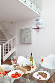 Set glass table below classic Verpan pendant lamp in open-plan interior with white-painted wooden staircase in background