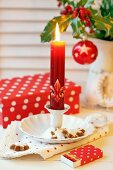 Advent arrangement of candlestick, cinnamon biscuits, matchbox with festive wrapping and gift box