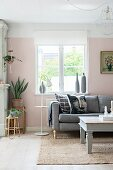 Kissen mit Gesichtsmotiv auf Polstersofa vor Fenster, seitlich Blumentöpfe auf schlichten Hockern in rosa getöntem Wohnzimmer mit romantischem Flair
