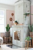 Concrete fireplace with chrome doors and house plants on rustic plant stands in corner of rustic living room