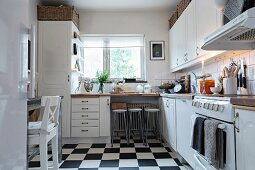 Bar stools at dining area below window and black and white chequered floor in white, Scandinavian fitted kitchen