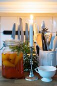Lit candle, pears in preserving jar and arrangement of fir twigs in front of kitchen utensils
