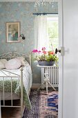 Flowering plants on side table next to ornate, white metal bed in romantic bedroom