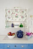 Detail of fruit bowl and blue ceramic pot on kitchen counter below decorative wall plates in plate rack mounted on wallpapered wall