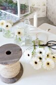 White gerbera daisies, small glass vases, vintage reel of string and garden scissors