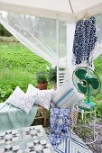 Garden pavilion furnished with bench, cushions and vintage fan on side table