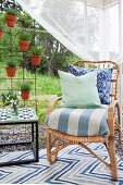 Scatter cushions on wicker chair with upholstered seat next to pots of lavender hung on rebar grille in garden pavilion