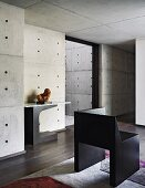 Room with dark wooden floor, modern art and exposed concrete walls an ceiling