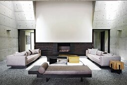 Modern double-height living room with concrete walls