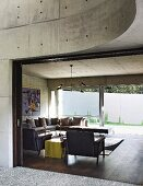 View into modern living room with concrete walls and glass wall