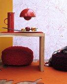Herbstliche Zimmerdeko mit orangenem blattförmigen Teppich, roten Sitzpoufs und Wandtapete mit Blättermotiv