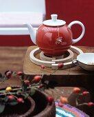 Rote Teekanne auf spiralförmigen Untersetzer aus Birkenholz
