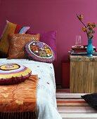 Indian Summer im Schlafzimmer: Bett dekoriert mit farbenfrohen Chenille- und Häkelkissen