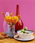 Porzellan und Vasen herbstlich dekoriert mit Dahlien und Kastanien