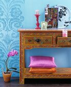 Accessories on console table richly decorated with floral pattern against blue wall