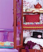 Brightly coloured, vintage accessories and clothing in open wooden cupboard with glass doors