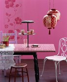 Mixture of styles in pink colour scheme: cake stand on dining table, various chairs and Oriental paper lanterns