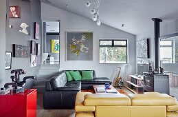 Black leather couch and yellow leather couch in open-plan, artistic interior with grey walls and gallery of pictures
