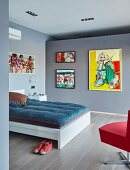 Double bed and gallery of modern paintings on wall of bedroom painted blue-grey