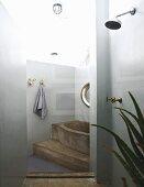 Betonierte Badewanne auf Podest, im Vordergrund Duschbereich