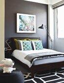 Schlafzimmer mit dunkelgrau getönter Wand, auf Doppelbett gestapelte Kissen, im Vordergrund Tierfigur auf Sitzpouf