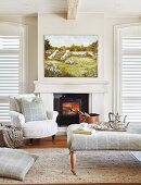 Armchair and ottoman in front of fireplace below oil painting in bright seating area